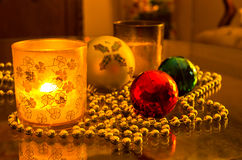 Christmas shiny colored decorations and candle in a glass Royalty Free Stock Image