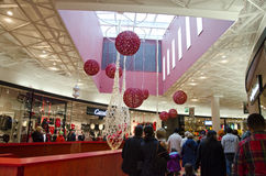 Christmas shoppers at the mall. Christmas on a busy day at the mall, shoppers are walking by the bright and decorated stores. Ornaments in red and white is stock photo
