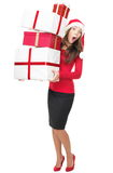 Christmas shopping. Santa woman standing holding gifts with funny expression isolated on white background. Young mixed race Asian Chinese / white Caucasian stock images