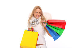 Christmas shopping. Beautiful blond female angel holding some colored shopping bags stock image