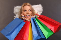 Christmas shopping. Beautiful blond female angel holding some colored shopping bags stock photos