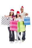 Christmas shopping. Happy multi racial family wearing Christmas hats and carrying shopping bags royalty free stock images