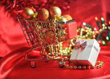 Christmas shopping. Still-life with trolley, seasonal ornaments and present Royalty Free Stock Photos
