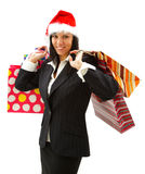 Christmas shopping. Smiling young businesswoman in santa hat with shopping bags Royalty Free Stock Photography