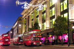 Christmas Shopping. Christmas lights on Oxford Street with the traditional red buses in front Selfridges Stock Photos