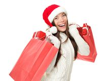 Christmas shopping. Woman holding shopping bags with gifts. Happy and smiling wearing red santa hat isolated on white background. Mixed race Caucasian / Chinese Stock Photography