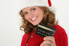 Christmas Shopping. Beautiful young woman in red sweater and santa hat holding up gold card.  Focus on card Royalty Free Stock Photo