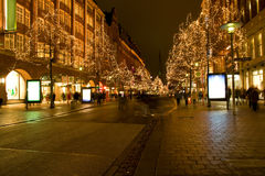 Christmas shopping. Christmas lights in trees along a street at night. People walking through the street and shopping. This is Mönckebergstraße in Hamburg stock photography