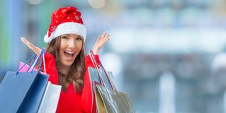 Christmas shopping. Attractive happy girl with credit card and s. Hopping bags in santa hat royalty free stock images