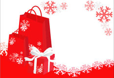 Christmas shopping background. Christmas shopping bags and gift with white ribbons on the snowflakes background Royalty Free Stock Photos