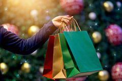 Christmas shopping bags in hand on christmas decoration h. Christmas shopping bags in hand on christmas decoration and light at night on street background Stock Photo