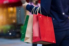 Christmas shopping - shopping bags in hand with snowflake. On Christmas decoration and lighting on street background royalty free stock photography