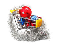 Christmas shopping. Christmas baubles inside shopping trolley on white background Royalty Free Stock Photography