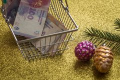 Christmas shopping / concept / christmas decorations and Argentinian money in the shopping cart. Expediture related to holidays / concept / decorations Stock Photo
