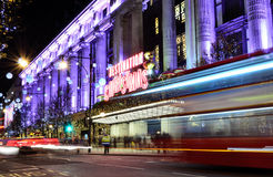 Christmas Shopping. December 16th , 2014: London, Selfridges Oxford Street. Christmas decorations and red buses passing by Selfridges Royalty Free Stock Images