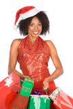 Christmas shopping (ethnic). Attractive tanned female in Santa hat with bags full of gifts Stock Photo