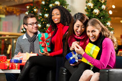 Christmas shopping - friends in mall. Diversity group of four people - Caucasian, black and Asian - sitting with Christmas presents and bags in a shopping mall royalty free stock images