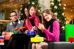 Christmas shopping - friends in mall. Diversity group of four people - Caucasian, black and Asian - sitting with Christmas presents and bags in a shopping mall stock photo