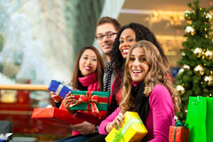 Christmas shopping - friends in mall. Diversity group of four people - Caucasian, black and Asian - sitting with Christmas presents and bags in a shopping mall royalty free stock photo
