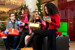 Christmas shopping - friends in mall. Diversity group of four people - Caucasian, black and Asian - sitting with Christmas presents and bags in a shopping mall Royalty Free Stock Photography