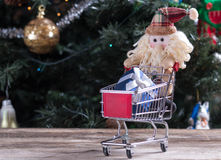 Christmas shopping. Funny Christmas character pushing shopping cart with gift Royalty Free Stock Image
