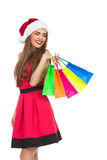 Christmas shopping. Christmas girl holding colorful shopping bags and looking over shoulder. Three quarter length studio shot isolated on white royalty free stock images