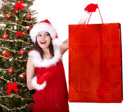 Christmas shopping of girl in santa hat, fir tree. Royalty Free Stock Photography