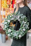 Christmas shopping. Green Christmas wreath in female hands. Decorated with gray elements, cotton and silver ball. Garland bokeh on background stock images