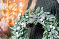 Christmas shopping. Green Christmas wreath in female hands. Decorated with gray elements, cotton and silver ball. Garland bokeh on background royalty free stock image
