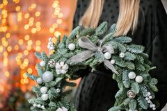 Christmas shopping. Green Christmas wreath in female hands. Decorated with gray elements, cotton and silver ball. Garland bokeh on background royalty free stock photos