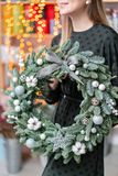 Christmas shopping. Green Christmas wreath in female hands. Decorated with gray elements, cotton and silver ball. Garland bokeh on background royalty free stock images