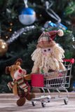 Christmas shopping. Happy Christmas characters pushing shopping cart Stock Photo
