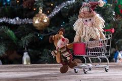 Christmas shopping. Happy Christmas characters pushing shopping cart Stock Photography