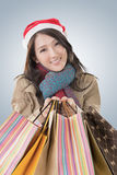 Christmas shopping. Happy shopping girl holding bags and wearing Christmas hat, half length closeup portrait Royalty Free Stock Photo