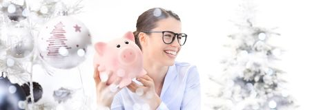 christmas shopping, laughing fun woman with piggy bank on blurred lights with tree and balls christmas background royalty free stock photography