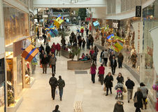 Christmas shopping in the mall. Shoppers stroll through a busy indoor shopping mall decorated for Christmas Royalty Free Stock Image