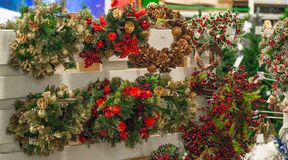 Christmas shopping. Many decorated with red elements and cones green christmas wreaths hanging in store for sale. Christmas shopping. Many decorated with red stock photos