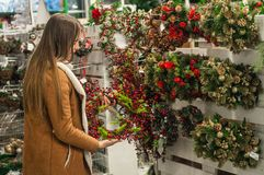 Christmas shopping. Many decorated, christmas wreaths hanging in store for sale. Green Christmas wreath on female hands. Christmas shopping. Many decorated with stock photo
