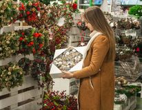 Christmas shopping. Many decorated, christmas wreaths hanging in store for sale. Green Christmas wreath on female hands. Christmas shopping. Many decorated with royalty free stock photography