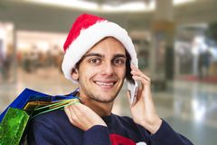 Christmas shopping and mobile phone. Portrait of Young with christmas shopping and mobile phone Stock Images