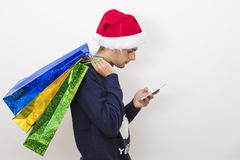 Christmas shopping and mobile phone. Portrait of Young with christmas shopping and mobile phone Royalty Free Stock Photo
