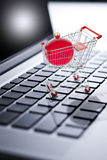Christmas Shopping Online Computer. A shopping cart with Christmas ornament on a laptop computer keyboard Stock Photo