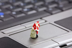 Christmas shopping online concept. Miniature Santa Claus standing on a laptop.  Christmas shopping online concept Royalty Free Stock Photos
