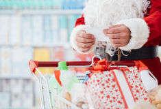 Christmas shopping. Santa Claus doing grocery shopping at the supermarket, he is pushing a full cart and checking a list, Christmas and shopping concept Royalty Free Stock Photos