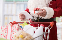 Christmas shopping. Santa Claus doing grocery shopping at the supermarket, he is pushing a full cart and checking a list, Christmas and shopping concept Stock Photo