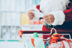 Christmas shopping. Santa Claus doing grocery shopping at the supermarket, he is pushing a full cart and checking a list, Christmas and shopping concept Stock Photos