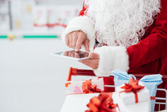 Christmas shopping. Santa Claus doing Christmas shopping at the supermarket, he is using apps on a digital tablet and pushing a cart filled with gift boxes Royalty Free Stock Photos