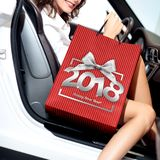 Christmas shopping, smiling woman with bag get in the car and ha Royalty Free Stock Photos