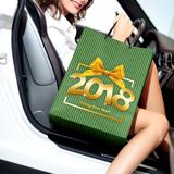 Christmas shopping, smiling woman with bag get in the car and ha. Ppy new year text in box frame with ribbon bow stock image