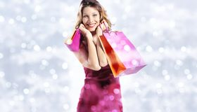Christmas shopping, smiling woman with bags on blurred bright li Royalty Free Stock Photos